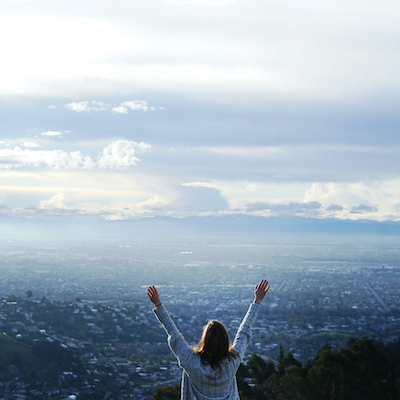 Raised hands over scenic view