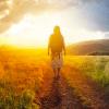 Woman wearing backpack walking on trail into sunrise