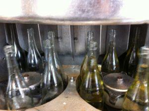 Unsere Flaschen gehen leer (links) in den Trommelfüller, und kommen mit unserem Secco befüllt (rechts) wieder raus...
