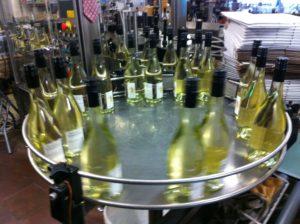 Die fertig befüllten, verschlossenen und etikettierten Flaschen warten auf dem Flaschenkaroussel auf das Verpacken