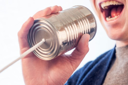 picture of a man speaking into a tin can telephone
