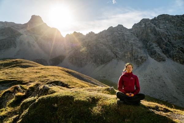Dominique sitzt meditierend am Fuße eines Gebirges