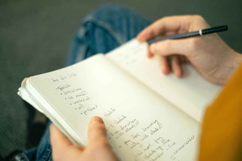 person writing a to do list