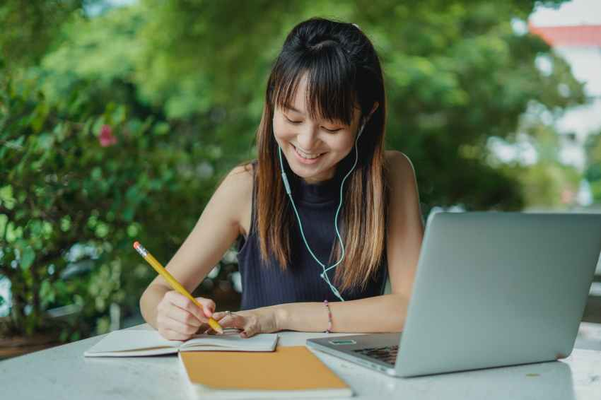 happy young asian student doing homework and listening to music with earphones