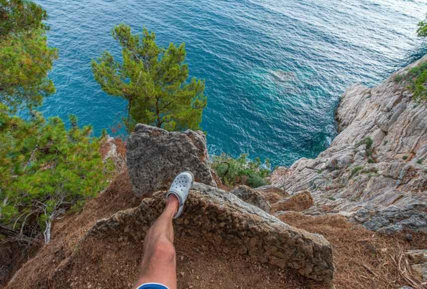 crop man standing on rock above sea