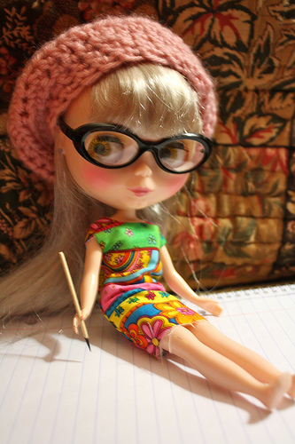 Doll with glasses and pencil
