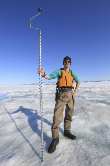 Adam on a warm and sunny day on the Milne Ice Shelf drilling holes in the ice.