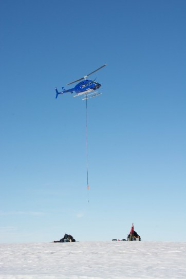 Derek guiding in helicopter pilot Mike Taekema during a camp move from the Milne Ice Shelf.