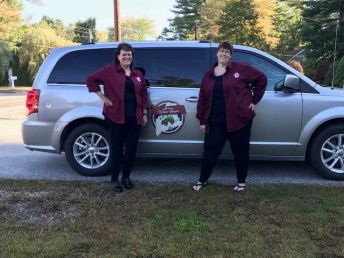 The owners of Mainery Wine Tours pose with their vehicle