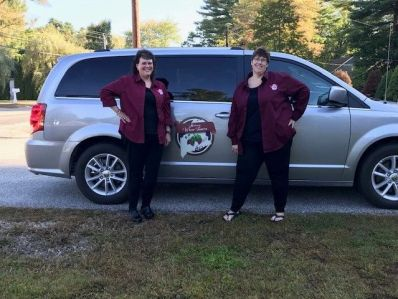 The owners of Maine Winery Tours pose by their vehicle.