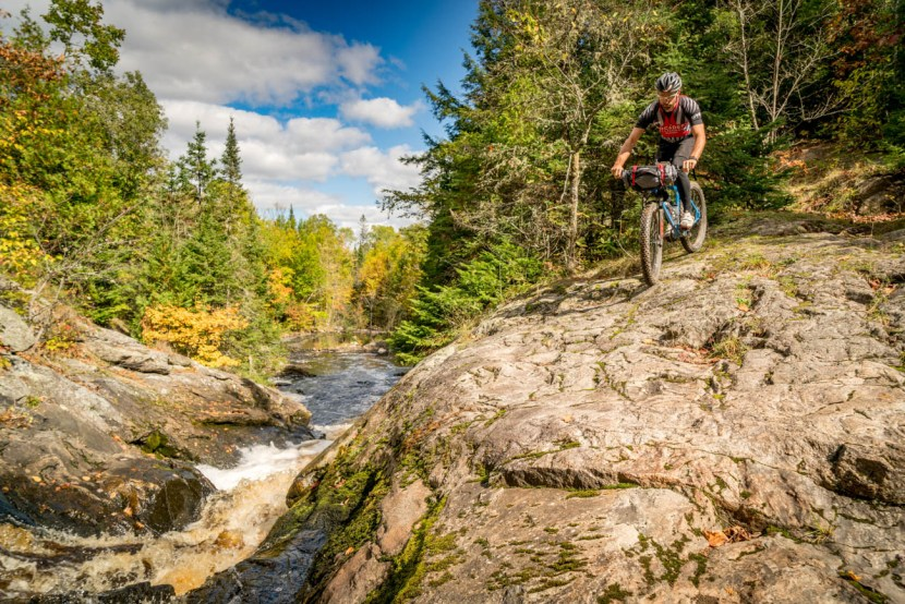 Bike rider on rocks next to waterfall