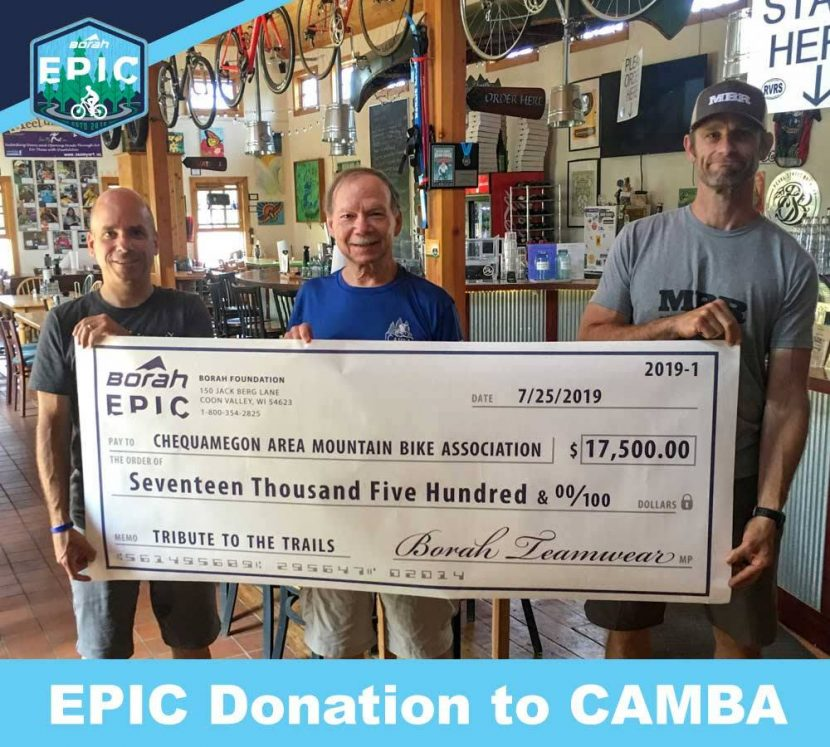 Three people hold giant check from Borah Epic to CAMBA for $17,500