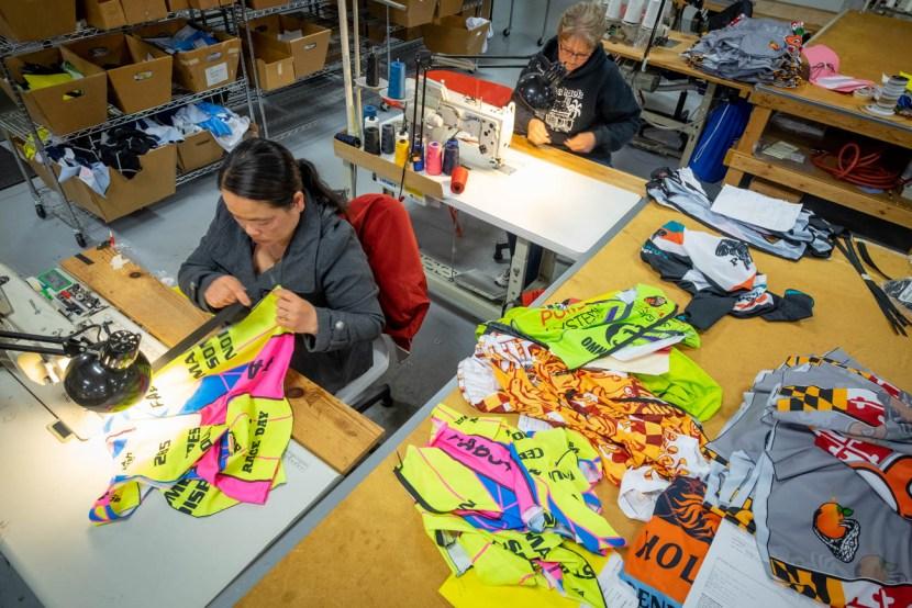 Two women sew jerseys