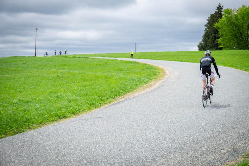 Riders pedal up a hill on a curvy road