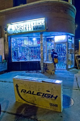 Two bike boxes on the sidewalk in the early morning outside a bike shop in Chicago