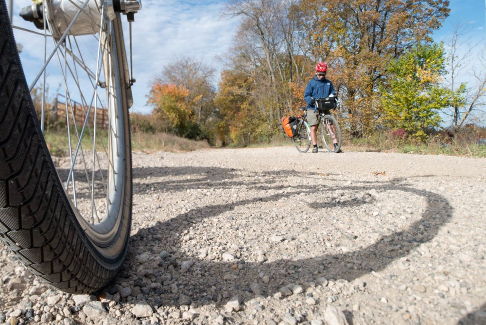 Bicycle tire in foreground with person on bike in background on gravel trail