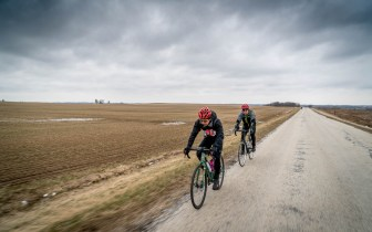 Two cyclists on an empty rural road with gray sky overhead