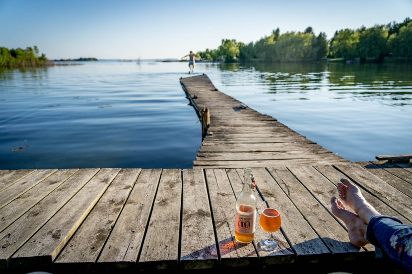Bottle and glass of cider next to crossed legs and bare feet on wooden pier on Washington Island with boy jumping into water in distance.