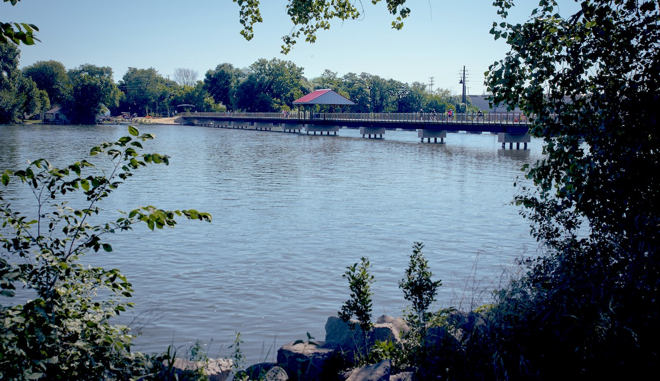Fox River and trestle bike bridge with bushes in foreground