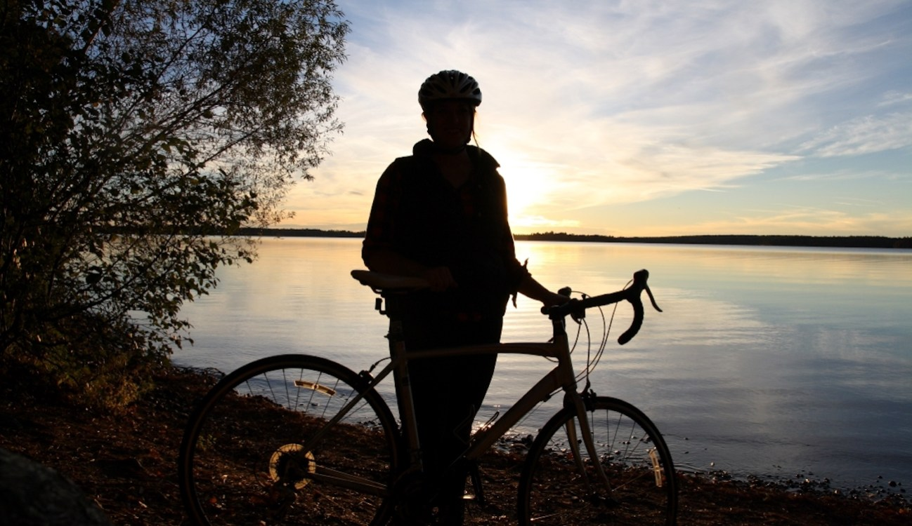 woman and bicycle silhouetted against sunset over inland lake
