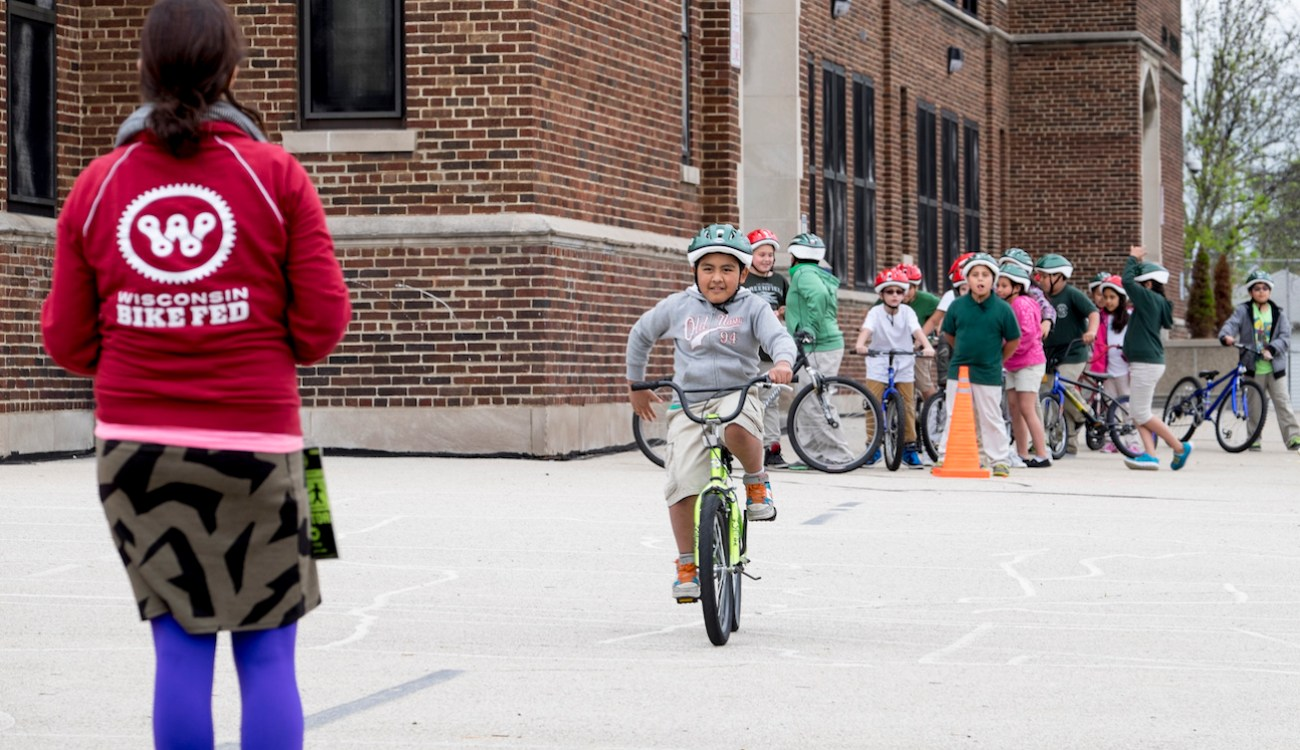 Bike Fed instructor on school playground teaching students how to signal stopping while riding a bicycle