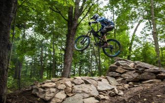 man jumping mountain bike over rocks