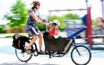 Woman riding a cargo bike with child in front past a playground