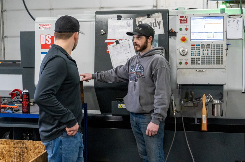 two men talk in front of a CNC machine