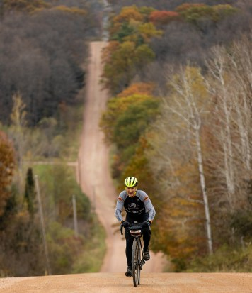 man riding up hill on gravel road