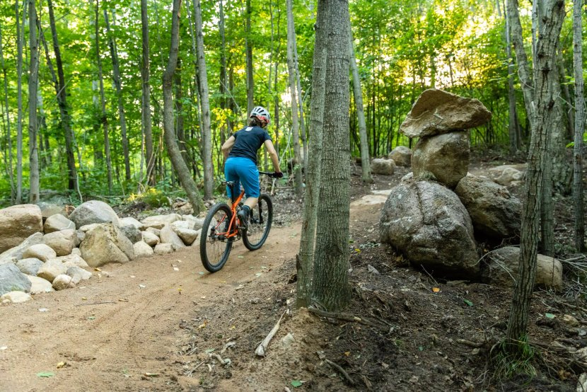 Woman riding a mountain bike away from camera in woods