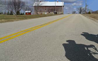 Shadow of riders on paved rural road with red barn in distance