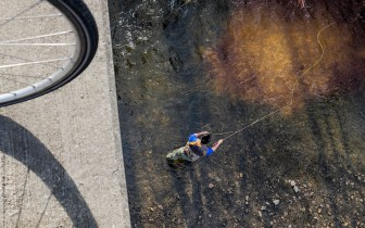 bicycle tire on bridge over man fly fishing in river below