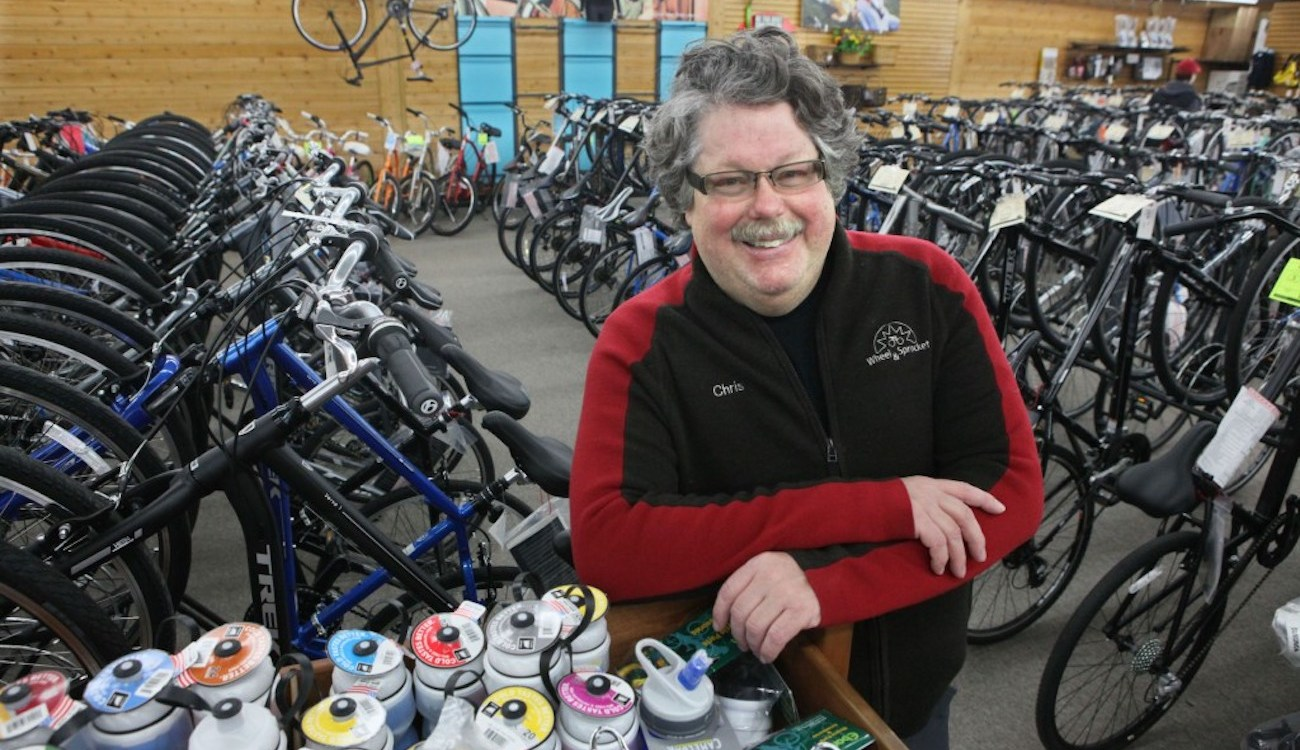 Chris Kegel leans on waterbottles with bikes behind him in the Hales Corners Wheel and Sprocket Store