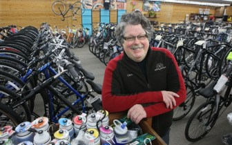 Chris Kegel leans on waterbottles with bikes behind him in the Hales Corners Wheel and Sprocket Store