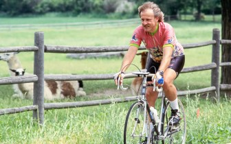 Phil Van Valkenberg rides his bicycle past two lamas lying down on the other side of a fence.