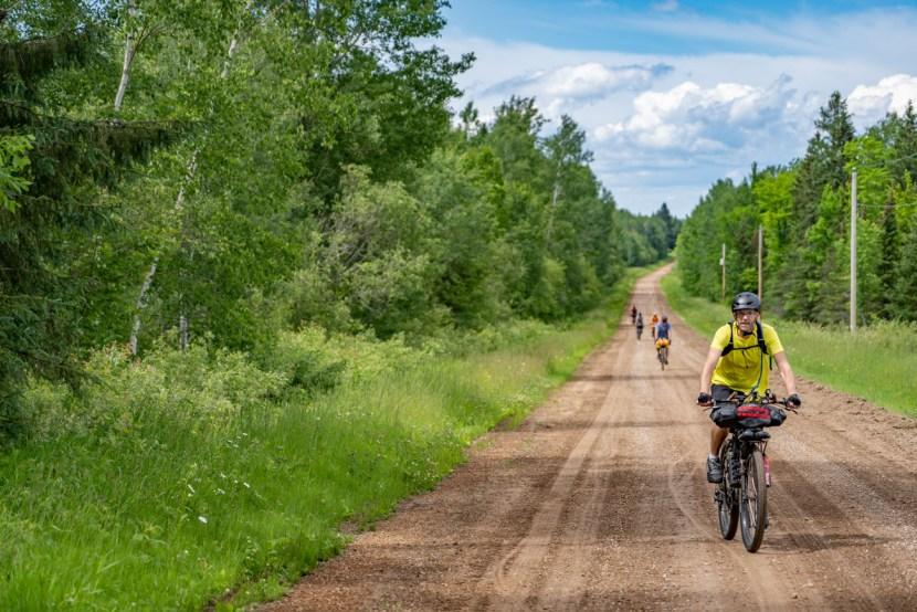 people on bicycles ride a gravel road at the camera