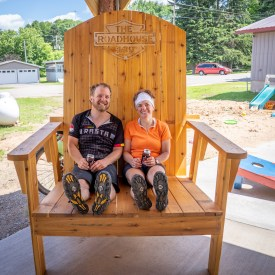 Husband and wife sit in an oversized wooden chair