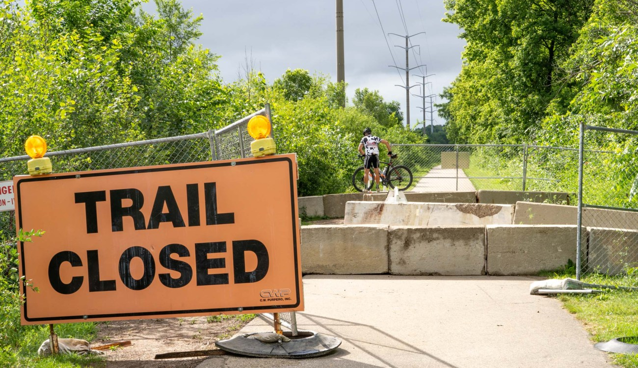 A person on a bicycle walks over concrete barriers past a trail closed sign
