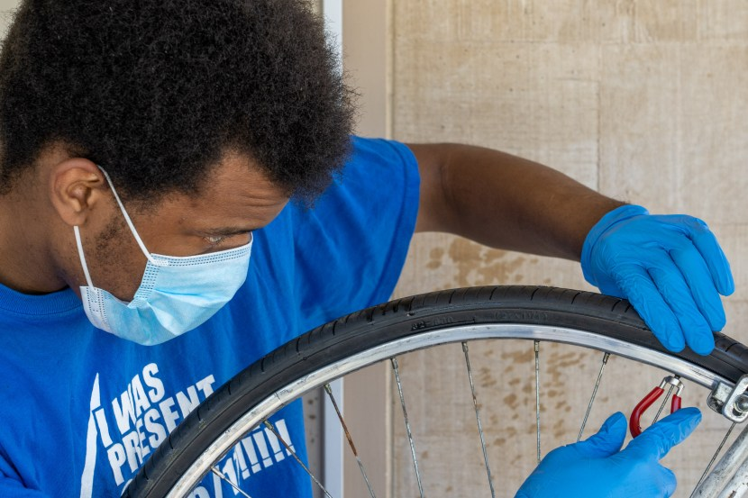 A young man wearing a mask trues a rear bicycle wheel with a spoke wrench