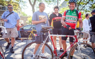Tom Schuler in 7-Eleven jersey stands next to his 7-Eleven Team Bike with others, laughing.