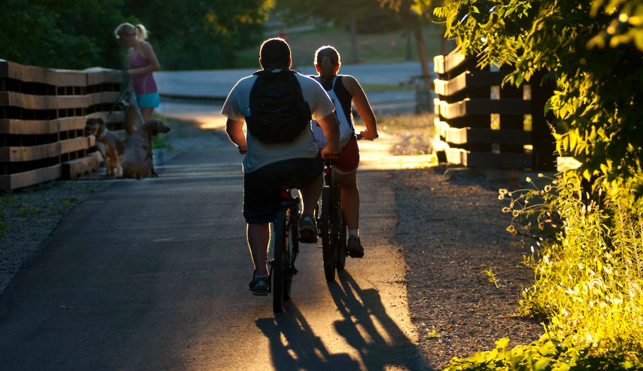 backlit photo of two kids riding bikes on trail and woman with dog on leash