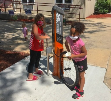 Two young residents learn about the Fix-It station just installed at Kennedy Heights in Madison