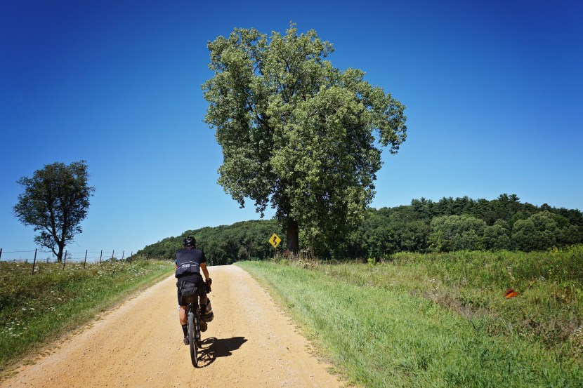 Art rides on gravel road under a perfectly clear blue sky.