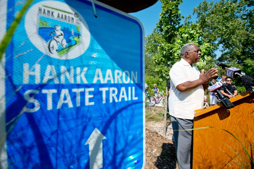Hank Aaron speaks at a podium with news microphones and a Hank Aaron State Trail sign in the foreground.