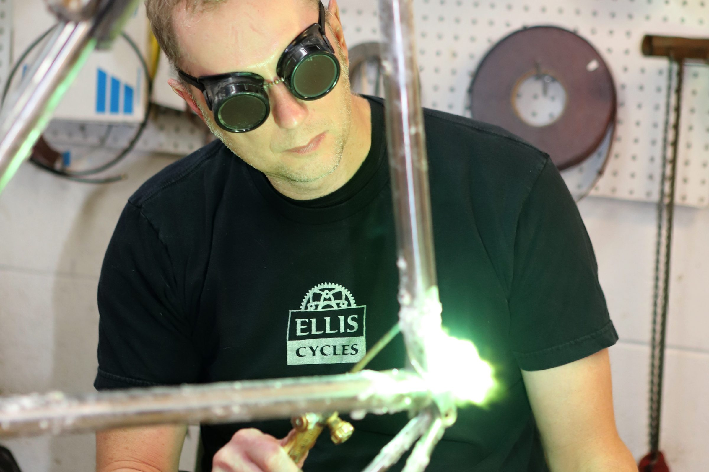 Dave Wages, wearing goggles, welds the top tube of the Schwinn Paramount