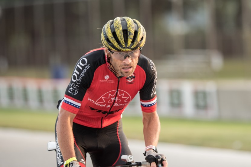 A racer pushes hard and grimaces as he pedals.