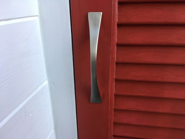 close-up of brushed silver handle on red closet door