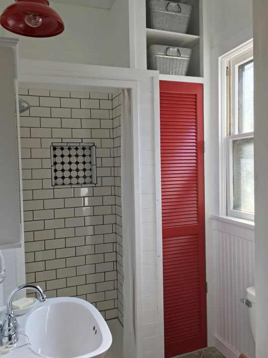 bathroom with white wood walls, subway-tiled shower stall and red accents