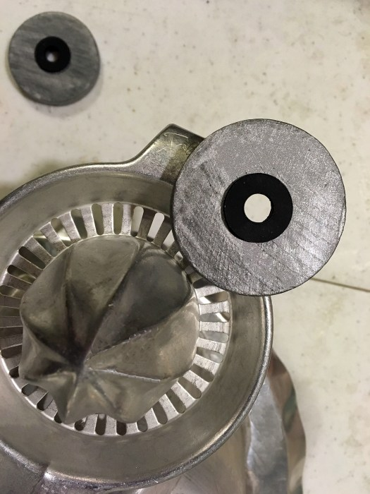 Junk turkey assemblage with metal eyes being placed on aluminum juicer face
