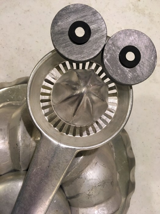 Vintage aluminum juicer that resembles a turkey face with two metal discs on it that look like eyes